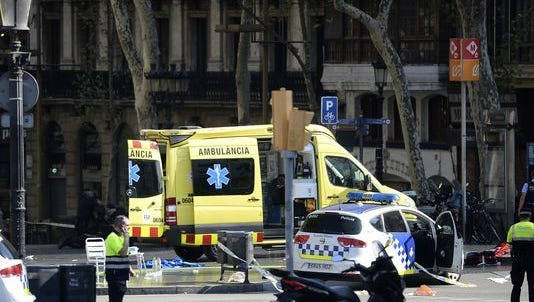 A policemen and a medical staff member stand past police cars and an ambulance in a cordoned off area after a van plowed into the crowd, injuring several people on the Rambla in Barcelona on August 17, 2017.