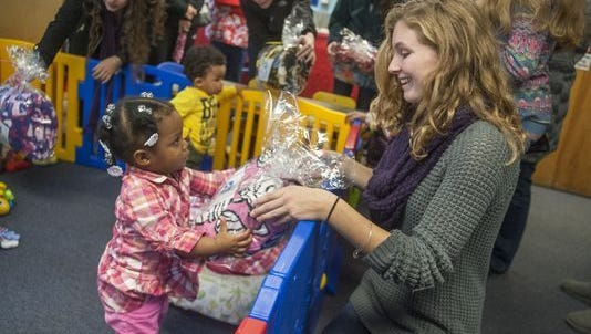 Megan Vizzard of Mount Laurel (front right), who created the nonprofit Cozies 4 Chemo, gives a blanket to Isis Hightower, of Camden, as Vizzard and other members of the Community Service Club of Lenape High School, deliver blankets from Cozies 4 Chemo to daycare students with medical needs at Providence Pediatric Medical DayCare in Virtua Camden in 2014.