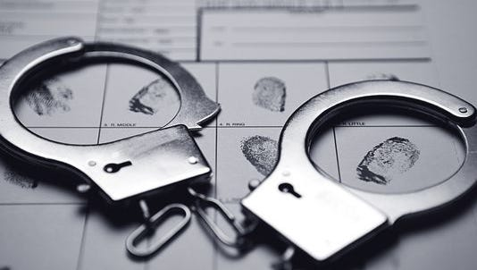 Handcuffs laid on top of a fingerprint card.