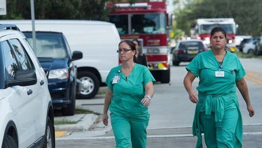 Health care workers walk down streets filled with emergency equipment near Memorial Regional Hospital after eight people died and more than 100 were evacuated at The Rehabilitation Center in Hollywood Hills because of intense heat and no power after Hurricane Irma.