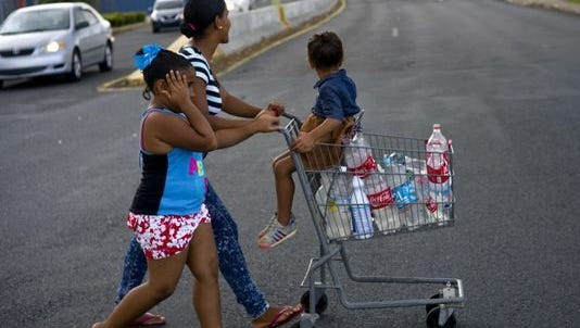 A resident collects water in Bayamon, Puerto Rico,  on Thursday.