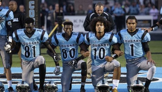 From left, Lansing Catholic's Kabbash Richards, Roje Williams, Michael Lynn III and Matthew Abdullah, knelt  during the national anthem before the start of the Cougars' home game on Oct. 6 against Ionia. None of the players started in the game.