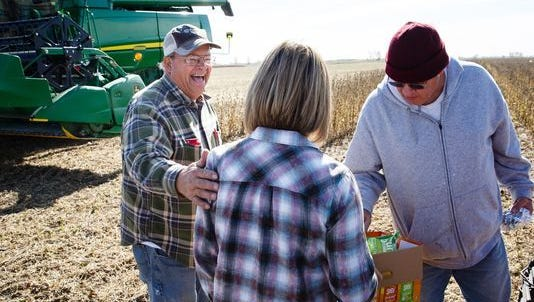 Larry Young, left, and his brother Roger Young, right, get lunch from Connie Brommel in the field on Wednesday, Oct. 25, 2017, in St. Charles. The pair were just a couple of the over 30 area farmers who showed up to help harvest the crop of Van Brownlee who passed away after planting in May.