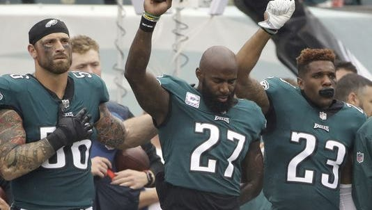 Eagles safety Malcolm Jenkins (27) joined by teammates Chris Long, left, and Rodney McLeod, has been raising his fist during the national anthem since Week 2 of the 2016 season. Jenkins resumed raising his fist during the national anthem on Thursday.