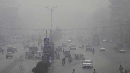 Motorcycles and vehicles are driven on a road while fog envelopes the area in Peshawar, Pakistan on Nov. 5, 2017. Smog has enveloped much of Pakistan and neighboring India, causing highway accidents and respiratory problems, and forcing many residents to stay home, officials said.