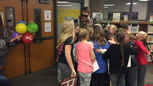 Beau Scott, a Dayton teacher, hugs his students after they give him a pair of sunglasses that allow him to see colors.