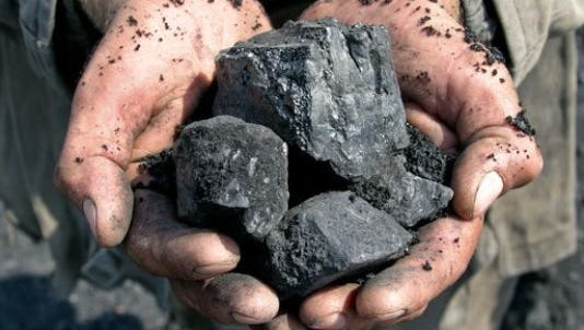 A coal miner holds chunks of coal in this undated photo.