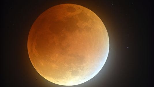 In this photo taken with a long exposure, Earth's shadow partially obscures the view of the so-called supermoon during a lunar eclipse in Stedman, N.C., on Sept. 27, 2015. It was the first time Sunday that the events have made a twin appearance since 1982, and they won't again until 2033.