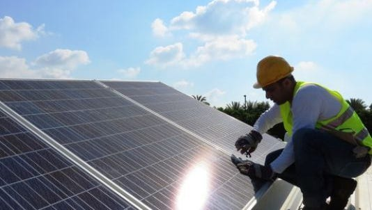 A worker installs solar system on a roof in this undated photo.