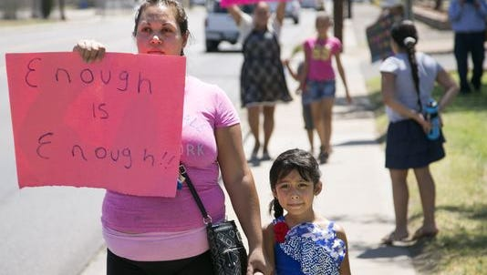 Angelica Zavala and her daughter, Thaily Chaga, 5, protest in front of the Murphy Elementary School District offices in Phoenix on July 13, 2016. Several dozen parents, including Zavala, withdrew their children from the district, saying the kids are not getting an adequate education.