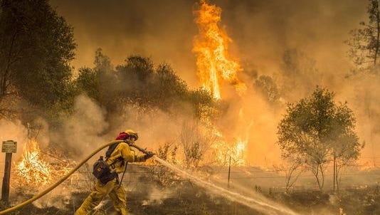 Firefighters battle wildfire near the town of Igo, California, on July 28.