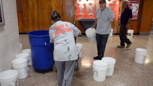 June Waldron (left), and Paul Montalto (center) work in Delsea Regional High School's lobby after heavy rainfall flooded sections of the building earlier this year.