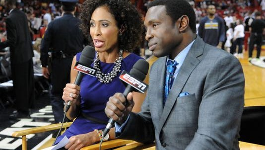 ESPN analyst Sage Steele (left) talks with analyst Avery Johnson courtside before the second half of a Dec. 18, 2013 game between the Indiana Pacers and the Miami Heat at American Airlines Arena.