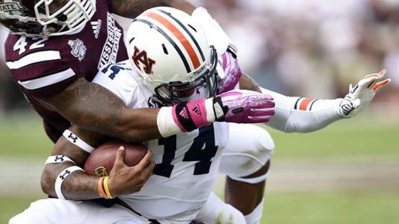 Mississippi State's Beniquez Brown tackles Auburn quarterback Nick Marshall.