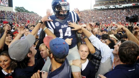 Ole Miss quarterback Bo Wallace (14) is carried off the field by fans following their 23-17 win over No. 3 Alabama.
