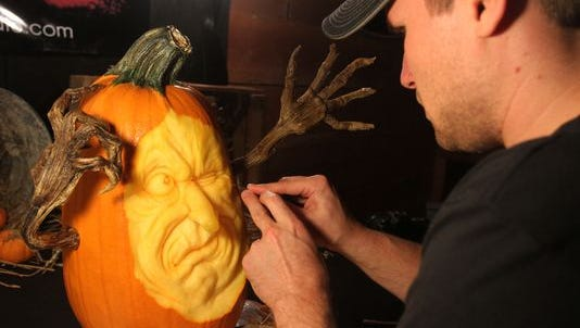 Mike Brown puts the finishing touches on a pumpkin. Though it will begin to rot in a couple days, Brown relies on photography to preserve his creation.