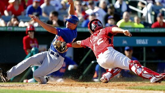JUPITER, FL - MARCH 2: Ed Easley #72 of the St Louis Cardinals tags Brandon Nimmo #77 of the New York Mets out at home in the eighth inning during a spring training game at Roger Dean Stadium on March 2, 2014 in Jupiter, Florida.