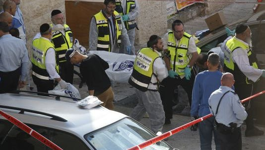 Israeli Zaka emergency services volunteers carry the body of a Palestinian assailant who was shot dead while attacking a synagogue in Jerusalem on Nov. 18.
