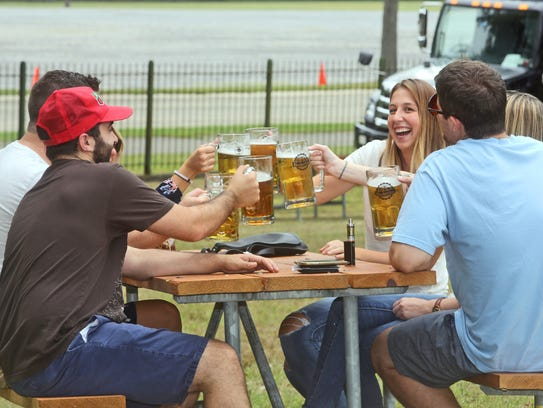 Friends raise their beer glasses for a toast as they