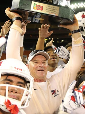Fresno State Bulldogs head coach Jeff Tedford holds up the trophy after his team beat the Houston Cougars 33-27 at the 2017 Hawaii Bowl at Aloha Stadium.
