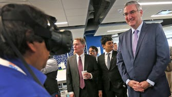 Gov. Eric Holcomb, right, smiles as Daniel Colon, left, demonstrates a virtual reality device for designing a home, during a tour at the ribbon cutting event for the Infosys tech and innovation hub, Tuesday, Mar. 6, 2018.