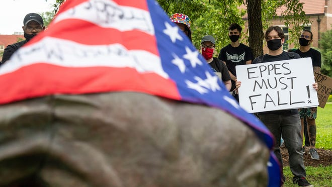 An American Flag with political messages written on it is draped over the statue of Francis Eppes on Saturday at the Florida State University campus as a crowd of more than 50 protesters gathers to demand that the statue be removed.