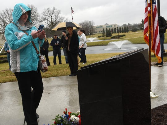 Tanya Elliott takes a photo of a memorial to Danville Police Officer Thomas Cottrell Jr. on the campus of Central Ohio Technical College. Elliott was the girlfriend of the Danville officer, who was shot and killed in the line of duty on Jan. 17, 2016, graduated from COTC in 2002.