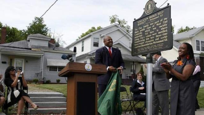 Louisville Metro Councilman David Tandy and Councilwoman Attica Scott unveil the marker during Tuesdayâ??s formal dedication at 3302 Grand Ave. Aliâ??s home is visible on the left.