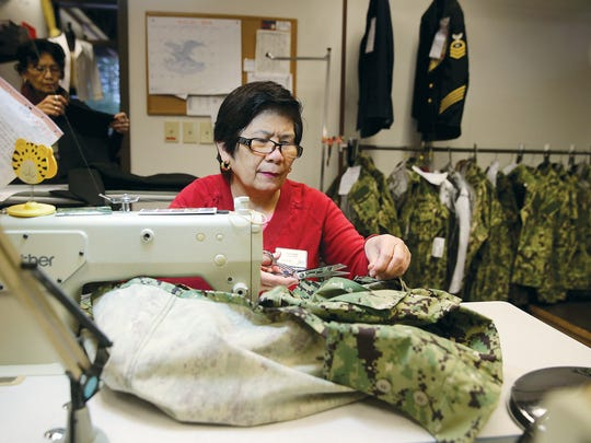 Taylor Maria Rosal works on a sailor's new green camouflage uniform NEX store on Naval Base Kitsap-Bangor. The Navy is changing from the blue camouflage to the green.