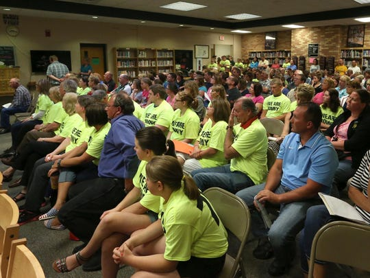 """People wearing """"We Are Jonny"""" T-shirts and others listen as a speaker talks about the bullying conditions in the Edgar school system at an Edgar School Board meeting."""