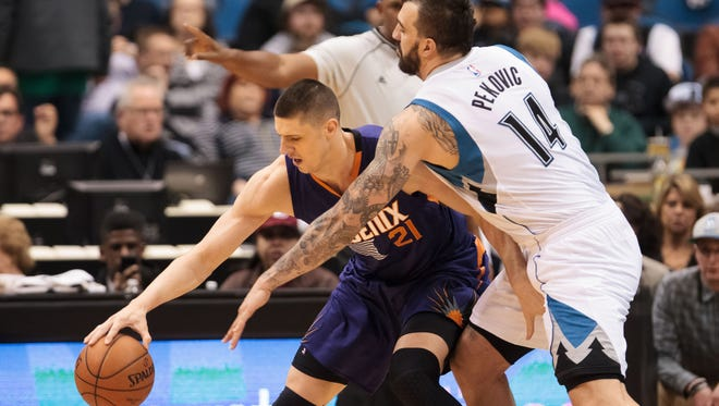Feb. 20, 2015: Timberwolves center Nikola Pekovic (14) tries to steal the ball from Suns center Alex Len (21) in the first quarter at Target Center.