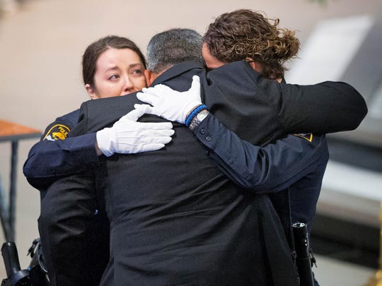 Two Omaha police officers embrace Hector Orozco, the husband of Kerrie Orozco, near the end of her funeral service at St. John's Catholic Church in Omaha, Neb.