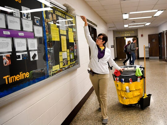 Kayla Brewington dusts the bulletin boards in the hallway in the student center at Tennessee Tech in Cookeville, Tenn., on Nov. 15, 2017. The janitor is a mother of four and said she wants to see more affordable health care.