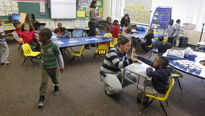 Nicole Berg, K-4 Principal, gives a high-five to kindergartener Brandon Fagan as she pops in to visit the class at the Urban Choice Charter School in Rochester.