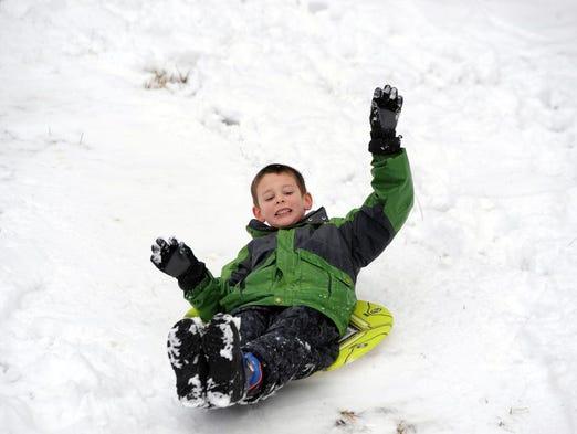 7-year-old Josiah Allen slides down a hill in Haw Creek