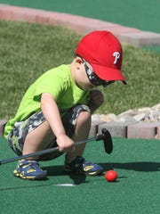 MINI GOLF OPENING: Matthew Emerson, 2, of Wilmington, tries out a hole Friday following the ribbon-cutting ceremony for Riverwalk Mini Golf along Wilmington's Riverfront, adjacent to the Delaware Children's Museum.