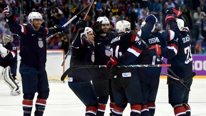 USA forward T.J. Oshie (74) is congratulated by his teammates after scoring the winning goal in an overtime shootout.