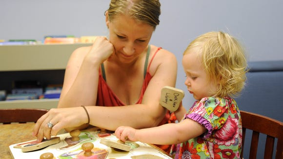 Rose Bickett helps her daughter Elyzah with a puzzle at Oak View LIbrary in Sioux Falls, S.D. Tuesday, July 21, 2015.