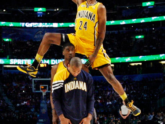 Indiana Pacers' Paul George jumps over two teammates during the NBA basketball All-Star Slam Dunk Contest in Orlando, Fla. Saturday, Feb. 25, 2012.