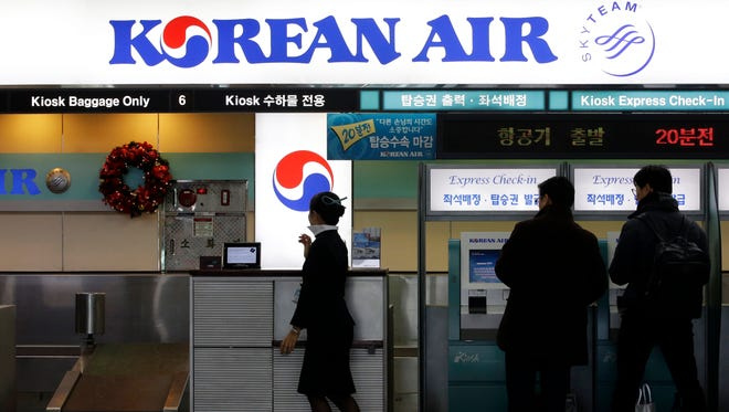 Passengers, right, are helped by an employee to check in at a Korean Air ticketing counter at Gimpo Airport in Seoul, South Korea, on Dec. 16, 2014.