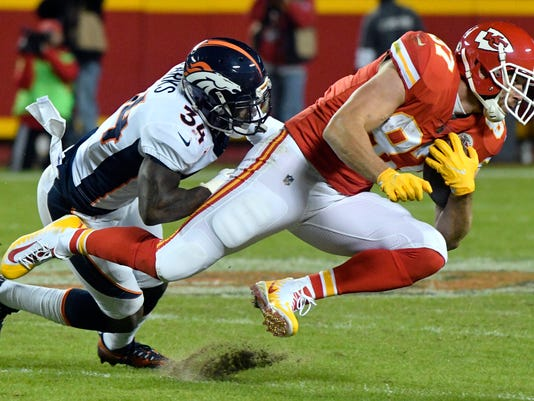 Kansas City Chiefs tight end Travis Kelce (87) is tackled by Denver Broncos safety Will Parks (34) during the second half of an NFL football game in Kansas City, Mo., Monday, Oct. 30, 2017. (AP Photo/Ed Zurga)