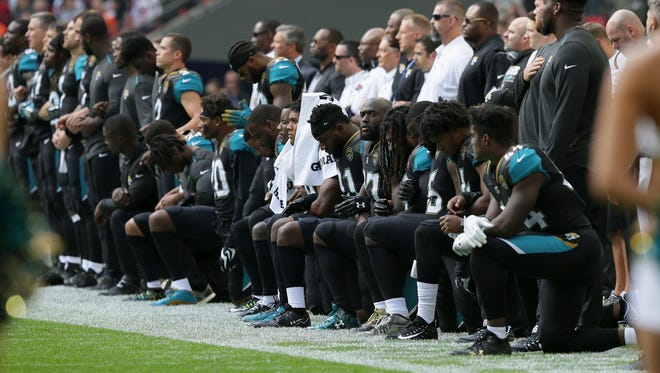 Jacksonville Jaguars players kneel down during the playing of the U.S. national anthem before an NFL football game against the Baltimore Ravens at Wembley Stadium in London.