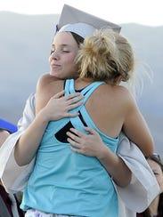 Salutatorian Abigail Sikora receives a hug from her