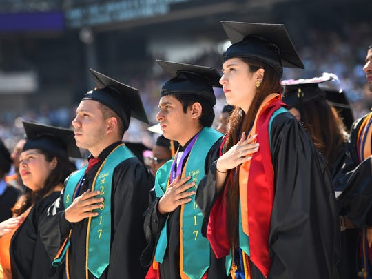 Daniela Liberato, right, listens to the singing of the National Anthem during the Bergen Community College commencement at MetLife Stadium in East Rutherford on Thursday.