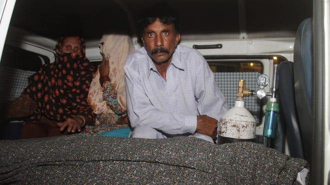 Mohammad Iqbal, right, husband of Farzana Parveen, 25, sits in an ambulance next to the body of his pregnant wife who was stoned to death by her own family in Lahore, Pakistan.