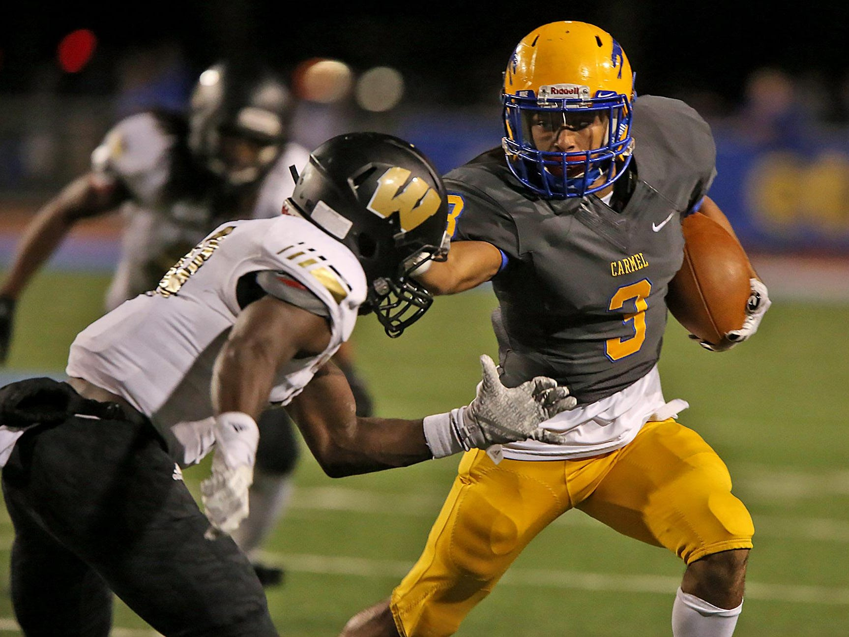 Carmel's #3 Jalen Walker makes a run as Warren Central's #19 Darien Rivers tries to stop him in second half during the Warren Central at Carmel High School football game, Friday, October 9, 2015. Carmel won 30-20.