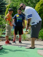 Mentor Spencer Hill shows Tyler, left, and Brendan the ins and outs of mini golf in Portland, Ore., on Tuesday, June 7, 2016.