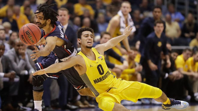Howard's Ausar Madison and Marquette's Markus Howard go after a loose ball Monday night.