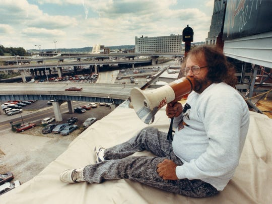 "SEPTEMBER 19, 1991: Dennis ""Wildman"" Walker, sports reporter for WEBN radio, sits on top of a billboard at 7th Street and Culvert Street and calls out to fans on a blowhorn as they walk by. Walker is staying on the billboard until the Bengals win a football game."