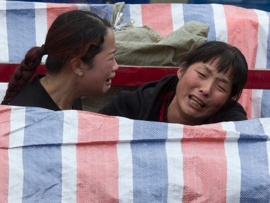 Women grieve near bodies covered by tarp at the site